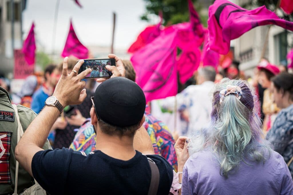 Myself in a purple t-shirt with pink XR flags in the background, next to a member of the public in a black t-shirt